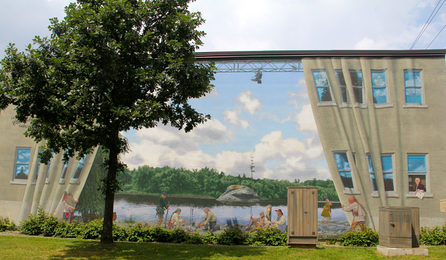 <p>Near 157, Bowen Nord Street<br />Wide: 68 feet<br />High: 29 feet<br />Realisation: MURIRS, 2010</p><p>This oversize mural presents facts and legends from the history of the Sherbrooke region. This scene is purely fictional.<br /><br />The foreground features the First Nations pulling back the existing wall like a theatre curtain. Most of these &quot;extras&quot; symbolize the succession of personalities, facts, and legends across several periods of our history, long before Sherbrooke or even Hyatt&rsquo;s Mill (name of the first village).<br /><br />The characters are assembled on the banks of the strategic Saint-Francis River, right in front of what has come to be a symbol of our region: the solitary pine.</p><p>&nbsp;</p>