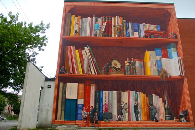 <p>Near 155, Belv&eacute;d&egrave;re nord street<br />Wide: 39 feet<br />High: 42 feet<br />Realisation: MURIRS, 2011</p><p>This mural evokes the history of a neighbourhood through culture, literature, and knowledge. The work brings together fact and fiction embroidered with the colours of the local former Lomas, Paton, and Kayser factories.<br /><br />This mural replaces the stories of the Coll&egrave;ge du Sacr&eacute;-Coeur high school with the levels of a bookcase housing tiny characters, in front of books from the literature of the Eastern Townships region.<br /><br />This mural is an allegory of Sherbrooke standing as a centre of knowledge, as well as a metaphor of the literary universe with more than 100 local authors represented. We can also see several historians of the region, and some of them are still alive.</p><p>&nbsp;</p>
