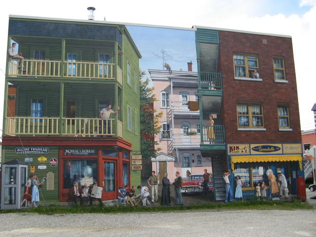 <p>Near 364, Alexandre&nbsp;Street<br />Wide: 57 feet &nbsp;<br />High: 34 feet<br />Realisation: MURIRS, 2005</p><p>This mural pays tribute to Sherbrooke&rsquo;s southwest district named &ldquo;Le Petit-Canada&rdquo; (Little Canada) and inhabited by French-Canadian workers. Illustrated here on September 27th 1957, this district was linked to the textile, mechanical engineering and metallurgy industries. The neighbourhood consisted mostly of large post war baby-boom families.<br /><br />This district included, at that time, square houses with large galleries, alleys and backyards, resulting in convivial neighbourhoods.<br /><br />At that time, Sherbrooke was becoming increasingly active with its burgeoning university and the arrival of new technologies, such as television.<br /><br />In this scene, a backdrop of Elvis Presley music, Chevrolet Bel-Air cars and the Sainte Flanelle set the stage for the appearance of a few local personalities and familiar merchants.</p><p>&nbsp;</p>