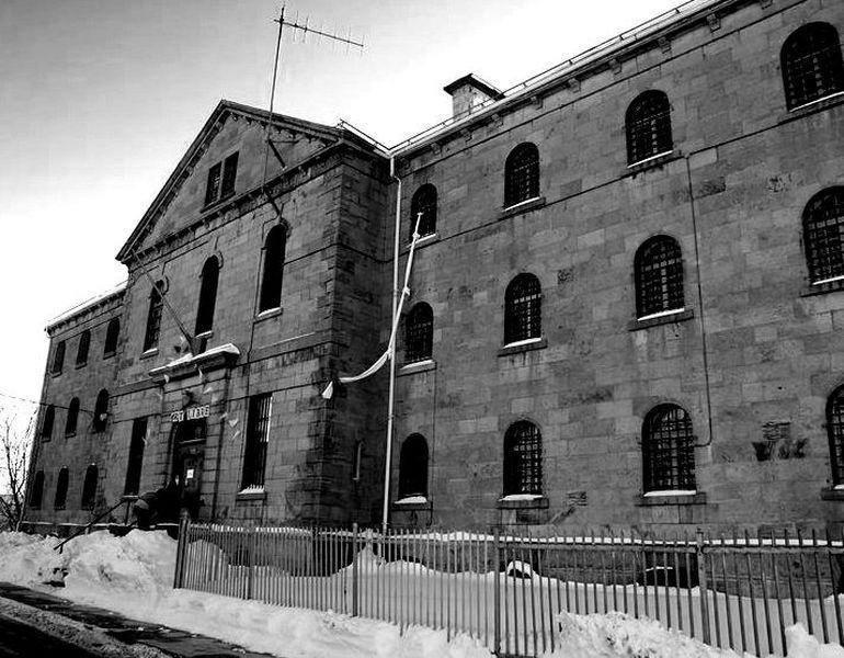 <p>Le d&eacute;but de la construction de la prison Winter date de 1865. La rue se nomme alors Jail Street (aujourd&#39;hui devenue la rue Winter). La prison se trouve juste &agrave; proximit&eacute; du Palais de justice de l&#39;&eacute;poque.<br /><br />Cette prison est le plus vieux b&acirc;timent de pierre de Sherbrooke. Elle comprend jadis 51 minuscules cellules simples ou doubles, une cuisine, une buanderie, une section pour les femmes, une section pour les travailleurs, quelques bureaux, un poste de contr&ocirc;le et une cour int&eacute;rieure.<br /><br />Une rumeur veut qu&#39;un tunnel souterrain secret reliait la prison et le Palais de Justice, alors situ&eacute; de l&#39;autre c&ocirc;t&eacute; de la rue.<br /><br />Des ex&eacute;cutions par pendaison avaient lieu dans la cour int&eacute;rieure.&nbsp;La premi&egrave;re ex&eacute;cution date du 10 d&eacute;cembre 1880:&nbsp;William Gray, journalier, y a &eacute;t&eacute; pendu pour le meurtre de Thomas Mulligan.&nbsp;Son corps est rest&eacute; suspendu durant dix longues minutes, m&ecirc;me s&#39;il &eacute;tait inerte depuis au moins quatre minutes.<br /><br />Source photo: Souvenirs de Sherbrooke et environs (Nath Doyon)</p>