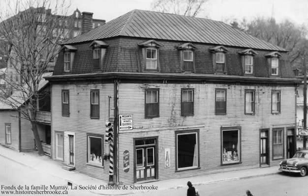 <p>Le Magasin g&eacute;n&eacute;ral de la famille Murray, dont trois g&eacute;n&eacute;rations accueillent des clients entre 1877 et 1953. Le commerce se sp&eacute;cialise dans le commerce de l&#39;avoine, du tr&egrave;fle et des graines de jardin. &Agrave; partir de 1885, le b&acirc;timent abrite aussi le premier bureau de poste de l&#39;Est de Sherbrooke. On reconnait aussi l&#39;&eacute;cole Saint-Jean-Baptiste &agrave; l&#39;arri&egrave;re.<br /><br />Source: Souvenirs de Sherbrooke et environs (Bernard Malenfant)</p>