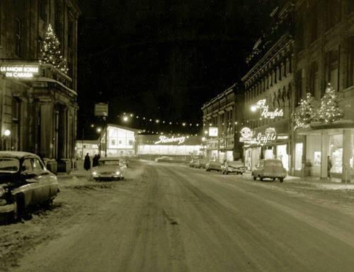 <p>Wellington en direction Nord, avec, &agrave; son extr&eacute;mit&eacute;, le magasin Steinberg, install&eacute; &agrave; cet endroit de 1953 &agrave; 1968. Le magasin repose alors sur des pieux, au dessus de la rivi&egrave;re.</p>