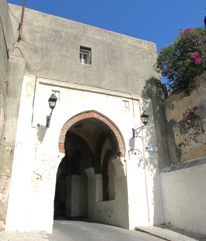 <p>Le mot Kashba est couramment utilis&eacute; dans cette partie de l&rsquo;Afrique. Il d&eacute;signe une ville fortifi&eacute;e, voire une citadelle. La porte de la Kasbah que nous apercevons a &eacute;t&eacute; construite au XVIII si&egrave;cle. On l&rsquo;appelait Peterbourough Gate pendant l&rsquo;occupation anglaise. Mais ce lieu est bien plus ancien. Ce fut jadis la porte d&rsquo;entr&eacute;e nord de la ville.&nbsp;</p>