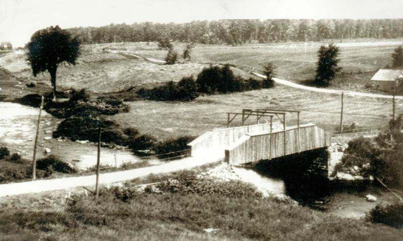 <p>Le pont de la rue Principale avec vue sur le boulevard Bromont et la place West-Shefford actuels. Photo prise apr&egrave;s 1904, ann&eacute;e o&ugrave; le pont pr&eacute;c&eacute;dant a &eacute;t&eacute; emport&eacute; par le courant puis reconstruit.&nbsp;</p>