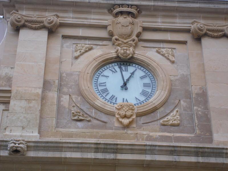 <p>La partie sup&eacute;rieure est orn&eacute;e d&rsquo;une horloge qui fut ramen&eacute;e sur l&rsquo;&icirc;le par le gouverneur anglais Richard Kane, en 1731, dix ans apr&egrave;s que la capitale ait &eacute;t&eacute; transf&eacute;r&eacute;e de Ciudadela &agrave; Mah&oacute;n, et que la mairie se soit install&eacute;e dans cet &eacute;difice jusque l&agrave; appel&eacute; La salle.</p>