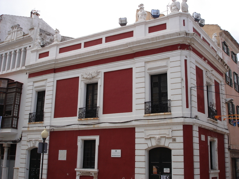 <p>You are facing the building known under the name of Principal de la Guardia, the edifice that housed the quarters of the British guardhouse in the 18th century, a location very representative of the English architecture in Mahon. Its red facade decorated with military motifs is part of the characteristics of the constructions in that era.</p>