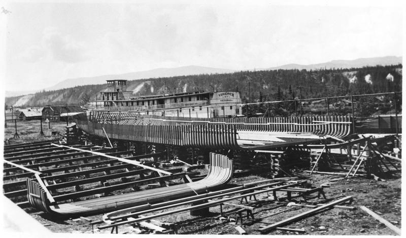 Les bateaux &agrave; aube ont beaucoup aid&eacute; Whitehorse &agrave; devenir la capitale qu&rsquo;elle est aujourd&rsquo;hui. Pendant presque cent ans, ces bateaux ont &eacute;t&eacute; les piliers du syst&egrave;me de transport du territoire. Introduits sur le fleuve Yukon en 1869, c&rsquo;est en 1898 que leur r&eacute;seau s&rsquo;est &eacute;tendu en aval de Whitehorse.<br /><br />La compagnie White Pass and Yukon Route (WPYR) a install&eacute; un chantier naval (shipyard en anglais) sur l&rsquo;emplacement de l&rsquo;actuel parc Shipyards en 1900-1901, pour construire et r&eacute;parer les bateaux qui naviguaient sur le fleuve Yukon. &Agrave; cette &eacute;poque, 400 &agrave; 500 ouvriers y travaillaient.<br /><br />Photo : S.S. Klondike en construction &agrave; Whitehorse, 1936. Le S.S. Yukoner est en arri&egrave;re-plan.<br />Cr&eacute;dit photo : Biblioth&egrave;que et Archives Canada, Iris Warner,&nbsp;C-034898