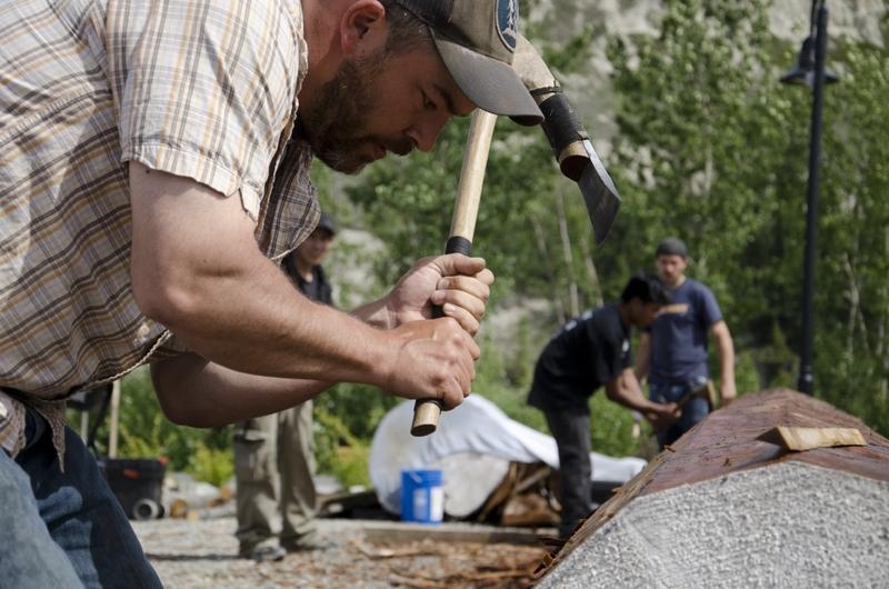<p>En 2013, vingt sculpteurs sur bois traditionnels de Northern Cultural Expressions Society (NCES) ont travaill&eacute; pendant vingt semaines pour fabriquer ce totem de gu&eacute;rison pour la communaut&eacute;, au bord du fleuve.<br /><br />Pendant le processus de cr&eacute;ation, chaque copeau de bois a &eacute;t&eacute; r&eacute;colt&eacute; puis br&ucirc;l&eacute; lors d&rsquo;une c&eacute;r&eacute;monie. Ils symbolisaient toutes les victimes des pensionnats, et aussi ceux qui ont subi les effets des drogues et de l&rsquo;alcool. Les cendres recueillies ont &eacute;t&eacute; introduites dans le totem.<br /><br />La communaut&eacute; s&rsquo;est rassembl&eacute;e pour transporter le totem du Kwanlin D&uuml;n Cultural Centre jusqu&rsquo;&agrave; son emplacement actuel. Autochtones, anglophones, francophones, pr&ecirc;tres, policiers, politiciens, tous ont port&eacute; le poids du totem pour affirmer leur volont&eacute; de commencer le processus de gu&eacute;rison ensemble.<br /><br />Photo : Sculpteurs sur bois de NCES<br />Cr&eacute;dit photo : NCES</p>