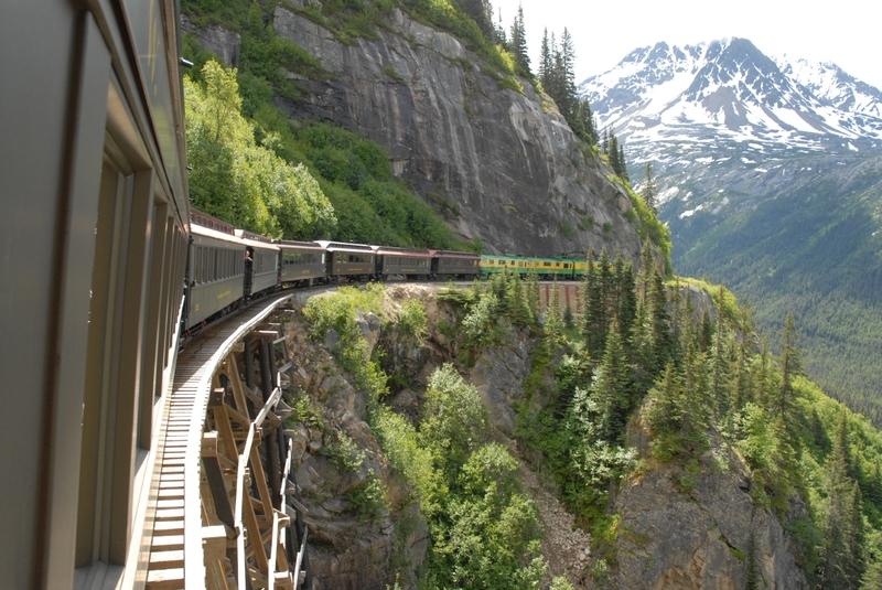 <p>Fond&eacute;e durant la Ru&eacute;e vers l&rsquo;or du Klondike, la compagnie White Pass &amp; Yukon Route (WP&amp;YR) a jou&eacute; un r&ocirc;le important dans le d&eacute;veloppement de Whitehorse. En 1901, elle a construit un chemin de fer qui reliait Skagway &agrave; Whitehorse, aujourd&rsquo;hui reconnu comme monument historique d&rsquo;ing&eacute;nierie civile.<br /><br />De l&agrave;, la compagnie a &eacute;rig&eacute; un v&eacute;ritable monopole en contr&ocirc;lant la totalit&eacute; du syst&egrave;me de transport : train, bateaux, autobus, camions&hellip; C&rsquo;est ainsi que Whitehorse est devenu pendant plusieurs d&eacute;cennies un centre d&rsquo;op&eacute;rations &eacute;troitement li&eacute; &agrave; la White Pass &amp; Yukon Route. Ce b&acirc;timent qui servait de d&eacute;p&ocirc;t &agrave; la compagnie illustre bien le lien historique entre ses divisions ferroviaire et fluviale.<br /><br />En 1982, la chute du cours des m&eacute;taux a entra&icirc;n&eacute; la fermeture de la ligne ferroviaire Whitehorse-Skagway, et du d&eacute;p&ocirc;t par le fait m&ecirc;me. Cinq ans plus tard, seule la portion entre Carcross et Skagway a &eacute;t&eacute; rouverte pour le tourisme.<br /><br />Photo : Train de la White Pass &amp; Yukon Route &agrave; travers les montagnes<br />Cr&eacute;dit photo : Gouvernement du Yukon</p>