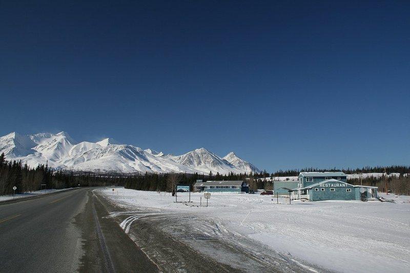 <p>Bear Creek (son nom traditionnel est Sh&auml;r T&aacute;g&agrave;ya), qui abrite aujourd&rsquo;hui une entreprise de coupe de bois, &eacute;tait &agrave; l&rsquo;origine un relais routier construit en 1906 le long de la &laquo; Kluane Wagon Road &raquo; par le Franco-Canadien Joseph Beauchamp. Il aurait &eacute;galement construit cinq autres cabines afin d&rsquo;encourager l&rsquo;installation de familles autochtones pr&egrave;s de son &eacute;tablissement, ce qui &agrave; l&rsquo;&eacute;poque &eacute;tait une pratique courante pour les commer&ccedil;ants.<br /><br />Sh&auml;r T&aacute;g&agrave;ya est devenu le lieu de r&eacute;sidence de familles autochtones pendant la premi&egrave;re moiti&eacute; du 20e si&egrave;cle. Les maisons &eacute;taient utilis&eacute;es de fa&ccedil;on semi-permanente lorsque les familles n&rsquo;&eacute;taient pas en train de chasser, de p&ecirc;cher ou de trapper. La communaut&eacute; a d&eacute;clin&eacute; avec l&rsquo;arriv&eacute;e de la route de l&rsquo;Alaska en 1942; la plupart des familles ont peu &agrave; peu d&eacute;m&eacute;nag&eacute; &agrave; Haines Junction.<br /><br />Photo : Bear Creek Lodge, 2006<br />Cr&eacute;dit photo : Murray Lundberg |explorenorth.com</p>
