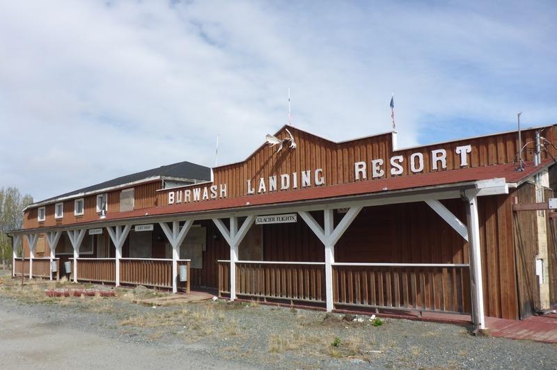 Les Jacquot dirigeaient un poste de traite au bord du lac qu&rsquo;ils avaient baptis&eacute; Burwash Landing, autour duquel d&rsquo;autres familles se sont install&eacute;es petit &agrave; petit pour former une communaut&eacute;. Le b&acirc;timent d&rsquo;origine du Burwash Landing Resort a &eacute;t&eacute; construit en 1948. Il regroupait un h&ocirc;tel, un restaurant, un magasin et le service de guidage de chasse. Eug&egrave;ne Jacquot a &eacute;t&eacute; le propri&eacute;taire et le g&eacute;rant de l&rsquo;h&ocirc;tel avec sa femme jusqu&rsquo;&agrave; sa mort, en 1950.<br /><br />&Agrave; l&rsquo;arri&egrave;re du b&acirc;timent, on peut apercevoir d&rsquo;anciens bateaux; ce sont les embarcations qu&rsquo;utilisaient les Jacquot dans les ann&eacute;es 1930-1940 pour traverser le lac, avant la construction de la route de l&rsquo;Alaska. L&rsquo;entreprise des Jacquot, la seule du coin, est demeur&eacute;e modeste jusqu&rsquo;&agrave; ce que l&rsquo;arm&eacute;e am&eacute;ricaine y installe un camp de base pour la construction de la route.<br /><br />L&rsquo;arriv&eacute;e &agrave; Burwash Landing &eacute;tait une b&eacute;n&eacute;diction pour les soldats; avec les l&eacute;gumes du jardin potager des Jacquot, le village se comparait &agrave; une oasis au milieu du d&eacute;sert. Sur la propri&eacute;t&eacute; se trouvait &eacute;galement une grange souterraine qui pouvait accueillir jusqu&rsquo;&agrave; 50 b&oelig;ufs.<br /><br />Cr&eacute;dit photo : St&eacute;phanie Chevalier&nbsp;