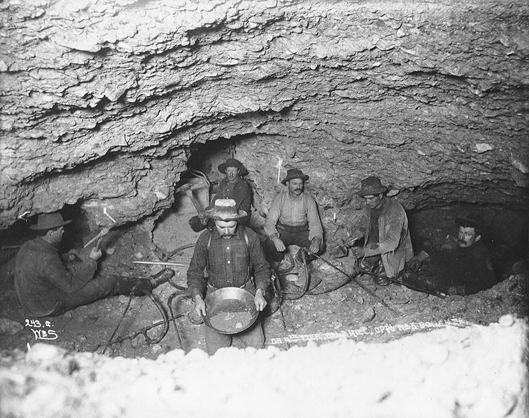 La route d&rsquo;Annie Lake a &eacute;t&eacute; construite pour acc&eacute;der aux mines du district de la rivi&egrave;re Wheaton, o&ugrave; de l&rsquo;argent avait &eacute;t&eacute; d&eacute;couvert en 1893. On y a &eacute;galement trouv&eacute; de l&rsquo;or, notamment sur la colline Gold, o&ugrave; 700 concessions mini&egrave;res ont &eacute;t&eacute; enregistr&eacute;es et quelques filons ont &eacute;t&eacute; exploit&eacute;s.<br /><br />Au bout de la route d&rsquo;Annie Lake, le mont Skookum a connu une p&eacute;riode active d&rsquo;exploitation de ses filons d&rsquo;or et d&rsquo;argent &agrave; la fin des ann&eacute;es 1980. Depuis, la r&eacute;gion vit surtout de l&rsquo;activit&eacute; d&rsquo;exploration, mais pas d&rsquo;exploitation.<br /><br />Photo : Des mineurs fondent le sol gel&eacute; dans une mine souterraine sur la colline Gold au Klondike, vers 1898.<br />Cr&eacute;dit photo : Universit&eacute; de Washington, coll. Eric A. Hegg