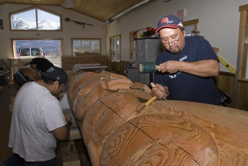 Le village de Carcross participe &agrave; la r&eacute;surgence des pratiques artistiques autochtones dont le territoire est t&eacute;moin ces derni&egrave;res ann&eacute;es. La sculpture a pris une part importante dans ce processus, avec l&rsquo;ouverture d&rsquo;un atelier en 2009.<br /><br />Le sculpteur local Keith Wolfe Smarch y travaille en &eacute;troite collaboration avec son fils, Erin Grey Wolf Smarch, sur des pi&egrave;ces d&rsquo;envergure. Leur style est inspir&eacute; de l&rsquo;art tlingit, du fait de la proximit&eacute; g&eacute;ographique, historique et culturelle des autochtones de la c&ocirc;te. Ils y enseignent aussi la sculpture aux jeunes d&eacute;sireux d&rsquo;explorer cette pratique artistique. Keith est un artiste de renomm&eacute;e internationale; ses &oelig;uvres sont install&eacute;es en Suisse, au Japon, en Australie, et font partie de la collection du palais de Buckingham.<br /><br />Si vous passez devant l&rsquo;atelier de sculpture et que la porte est ouverte, entrez! Vous pourrez voir les artistes &agrave; l&rsquo;&oelig;uvre et discuter avec eux de leurs cr&eacute;ations.<br /><br />Photo : Sculpteurs dans l&rsquo;atelier<br />Cr&eacute;dit photo : Gouvernement du Yukon