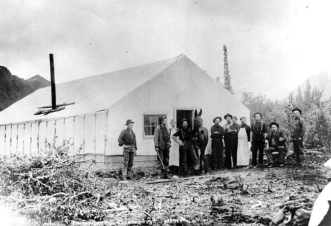 La saison suivante, Conrad employait plus de 500 hommes et Conrad City &eacute;tait une communaut&eacute; anim&eacute;e, avec six h&ocirc;tels, des magasins et un acc&egrave;s r&eacute;gulier &agrave; Carcross par bateau &agrave; aubes. En 1909, Conrad City abritait 3&thinsp;000 habitants.<br /><br />Mais le succ&egrave;s de Conrad n&rsquo;a pas persist&eacute;. Le minerai extrait du mont Montana s&rsquo;av&eacute;rait de qualit&eacute; in&eacute;gale, et Conrad a intent&eacute; un proc&egrave;s &agrave; la White Pass &amp; Yukon Route qui lui faisait payer cinq fois plus cher que n&rsquo;importe quel service de fret sur le continent. La bataille a dur&eacute; des ann&eacute;es et Conrad l&rsquo;a perdue.<br /><br />Avec les probl&egrave;mes financiers de la mine et le prix de l&rsquo;argent en d&eacute;clin, Conrad a quitt&eacute; le Yukon en 1912. Une grande partie des infrastructures ont &eacute;t&eacute; d&eacute;plac&eacute;es &agrave; Carcross qui &eacute;tait en reconstruction apr&egrave;s un important incendie en 1909.<br /><br />Photo : Des hommes au Vancouver Hotel &agrave; Conrad City, en 1905.<br />Cr&eacute;dit photo : Archives du Yukon, Fonds Jack Stewart, 95/98 # 7