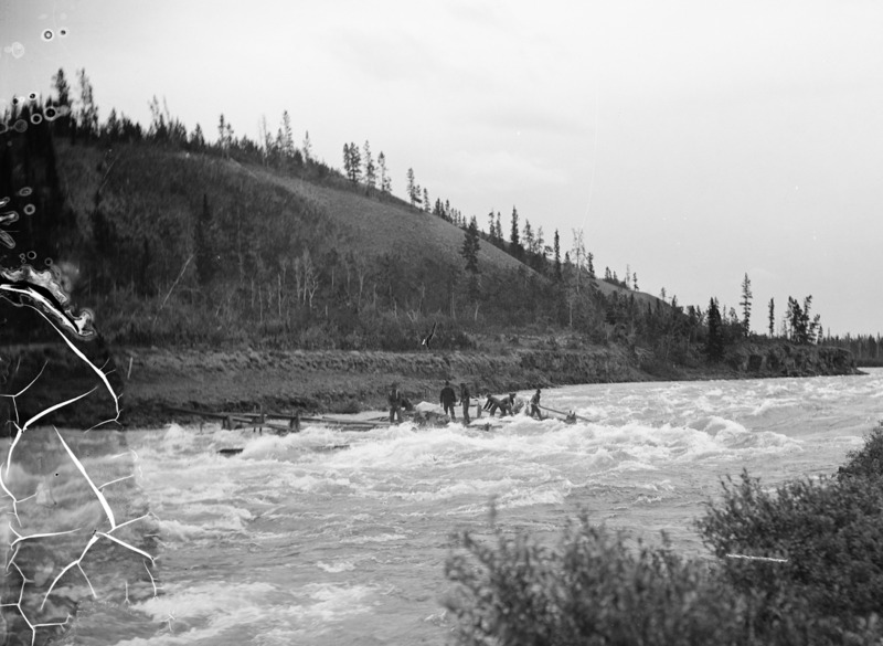 Avant la construction du barrage hydro&eacute;lectrique en 1958, les rapides du cheval blanc commen&ccedil;aient &agrave; l&rsquo;emplacement actuel du lac Schwatka, plus en amont, et s&rsquo;&eacute;tendaient presque jusqu&rsquo;au SS Klondike. L&rsquo;&eacute;cume des rapides faisait penser &agrave; la crini&egrave;re de chevaux blancs, ce qui a donn&eacute; le nom White Horse &agrave; la ville, qui plus tard est devenue Whitehorse. Contrairement &agrave; ce que l&rsquo;on pourrait croire, les rapides &eacute;taient plus p&eacute;rilleux que le canyon Miles.<br /><br />Lorsque le fleuve s&rsquo;est lib&eacute;r&eacute; de la glace au printemps de 1898, &agrave; peine quelques jours apr&egrave;s l&rsquo;arriv&eacute;e de la vague de chercheurs d&rsquo;or au canyon Miles, au moins 150 embarcations ont &eacute;t&eacute; d&eacute;truites dans les rapides de White Horse et dix personnes se sont noy&eacute;es.<br /><br />&laquo; Nous voici bient&ocirc;t engag&eacute;s dans les rapides, un peu moins longs que le Cagnon (canyon), mais plus dangereux peut-&ecirc;tre; les eaux resserr&eacute;es dans un &eacute;troit chenal bondissent en montagnes d&rsquo;&eacute;cume roulant sur d&rsquo;&eacute;normes blocs de roche o&ugrave; se sont bris&eacute;s maints esquifs, et o&ugrave; ont p&eacute;ri maints &eacute;quipages. &raquo;<br />L&eacute;on Boillot, Aux mines du Klondike : du lac Bennett &agrave; Dawson City, 1899<br /><br />Photo : Hommes sur un radeau dans les rapides de White Horse<br />Cr&eacute;dit photo : Alaska State Library, coll. James Wickersham Photographs, 1882-1930 s, Hegg, E. A. (sign&eacute;e par Larss &amp; Duclos), p277_001_017