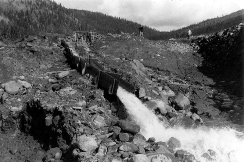 La route sur votre gauche (ouest) m&egrave;ne au ruisseau Haggart et au ravin Dublin, une r&eacute;gion connue depuis le d&eacute;but du 20e si&egrave;cle pour son gisement d&rsquo;or.<br /><br />Le Yukon est une r&eacute;gion g&eacute;ologiquement active qui contient une large vari&eacute;t&eacute; de ressources min&eacute;rales. Comme la couche sup&eacute;rieure de terre est mince dans une grande partie du territoire &agrave; cause du froid et du climat sec, les gisements de minerai sont proches de la surface. Les ravins, les bords de ruisseaux et de lacs se r&eacute;v&egrave;lent de bons sites o&ugrave; prospecter.<br /><br />Photo : Bo&icirc;te d&rsquo;&eacute;cluse utilis&eacute;e dans l&rsquo;exploitation de placers dans le ruisseau Haggart, au ravin Dublin, 1953<br />Cr&eacute;dit photo : Peter Tarassoff, mindat