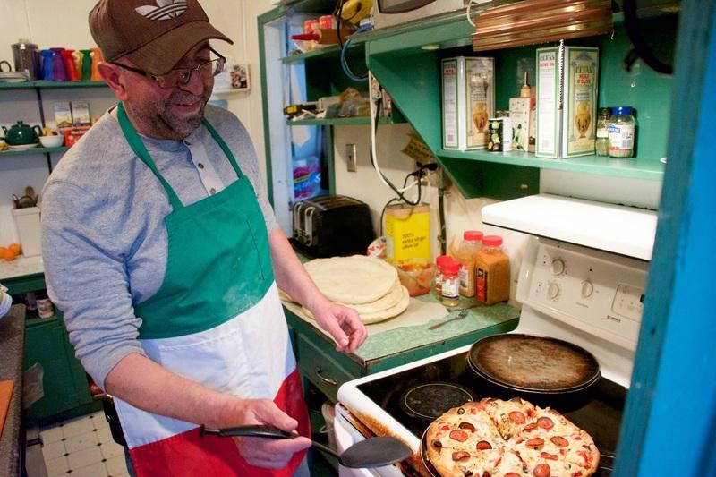 Mike Mancini, le propri&eacute;taire du Keno Snack Bar, est un enfant du pays. N&eacute; de parents italiens qui se sont install&eacute;s &agrave; Elsa pour que son p&egrave;re travaille &agrave; la mine, il a lui aussi eu l&rsquo;occasion de s&rsquo;essayer &agrave; toutes sortes d&rsquo;emplois &agrave; la mine et il a ador&eacute; &ccedil;a.<br /><br />Apr&egrave;s quelques ann&eacute;es pass&eacute;es &agrave; &eacute;tudier le fran&ccedil;ais et l&rsquo;italien &agrave; Edmonton, puis &agrave; travailler dans un studio de t&eacute;l&eacute;vision mobile sur l&rsquo;&icirc;le de Vancouver, c&rsquo;est une cabine re&ccedil;ue en h&eacute;ritage qui l&rsquo;a ramen&eacute; &agrave; Keno. Son amour de la r&eacute;gion &eacute;tait grand et il y a trouv&eacute; un groupe de personnes pr&ecirc;tes &agrave; collaborer ensemble pour pr&eacute;server le patrimoine des mines de la r&eacute;gion, si bien qu&rsquo;il y est rest&eacute;, et ne compte pas en repartir.<br /><br />Photo : Mike dans sa cuisine<br />Cr&eacute;dit photo : Johan Demarle