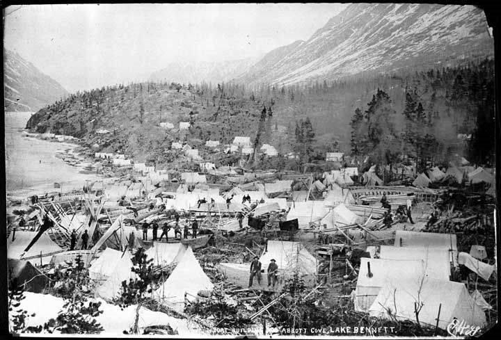 Le village de Bennett, du fait de son emplacement strat&eacute;gique situ&eacute; &agrave; l&rsquo;extr&eacute;mit&eacute; sud du lac du m&ecirc;me nom, a &eacute;t&eacute; le plus grand campement semi-permanent durant la Ru&eacute;e vers l&rsquo;or, entre la fin de la piste Chilkoot et le lac Bennett.<br /><br />Durant l&rsquo;hiver de 1897-1998, 20&thinsp;000 hommes inexp&eacute;riment&eacute;s ont construit 7&thinsp;000 bateaux en attendant la d&eacute;b&acirc;cle du printemps pour rejoindre Dawson.<br /><br />Photo : Construction de bateaux dans la crique, Lac Bennett, ca. 1898.<br />Cr&eacute;dit photo : Alaska State Library, Collection P. E. Larss, 1898-1904. ASL-PCA-41, ASL-P41-175, Photographe Hegg, Eric A.
