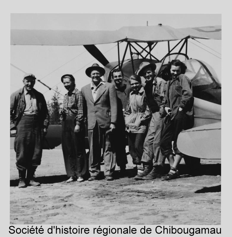 <p>&laquo;Scotty &raquo; Stevenson (1912-1974) est le pilote du Nord le plus connu de l&rsquo;histoire de Chibougamau. N&eacute; en &Eacute;cosse, il arrive au Qu&eacute;bec en 1927. Il a d&rsquo;abord &eacute;t&eacute; pilote pour la Compagnie de la Baie d&rsquo;Hudson, puis pilote de chasse lors de la Seconde Guerre mondiale.<br /><br />Apr&egrave;s la guerre, il entame sa carri&egrave;re de pilote ind&eacute;pendant et de commer&ccedil;ant dans le Nord du Qu&eacute;bec. Il &eacute;change des fourrures avec les trappeurs autochtones et il participe au d&eacute;veloppement minier, transportant prospecteurs, g&eacute;ologues et promoteurs miniers avec leur mat&eacute;riel.<br /><br />Scotty Stevenson est pass&eacute; &agrave; la l&eacute;gende pour ses atterrissages sur la 3e Rue, au d&eacute;but des ann&eacute;es 1950. Certaines revues prestigieuses publi&egrave;rent des articles &agrave; son sujet, dont le Time Magazine.<br /><br />En 1950, Scotty Stevenson ouvre le premier magasin g&eacute;n&eacute;ral de Chibougamau, le minuscule Eastern Trader. Il fondra plus tard l&#39;h&ocirc;tel Waconichi Inn. Vous trouverez plus d&#39;information &agrave; ce sujet au point d&#39;int&eacute;r&ecirc;t num&eacute;ro 8.<br /><br />R&eacute;f&eacute;rence compl&egrave;te pour la photo: photo de groupe devant l&#39;avion Fox Moth CF-EXW de Scotty Stevenson, en 1950. De gauche &agrave; droite: Lorenzo Blondeau, Eileen Stevenson, Scotty Stevenson, Andr&eacute; Tison, Gis&egrave;le Cire, Amy Lee et personne non identifi&eacute;e.<br />P24 Fonds Frederick Nelson Bidgood.</p>