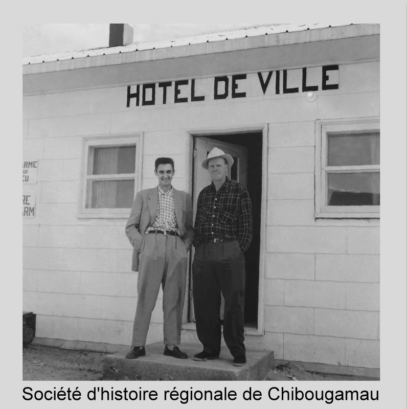<p>En 1952, le village de Chibougamau est officiellement fond&eacute;. Il porte alors le nom de &laquo;Municipalit&eacute; du Centre Minier de Chibougamau&raquo;. Comme le village se peuple et qu&rsquo;il faut organiser des services municipaux plus ad&eacute;quats, Chibougamau devient ville en 1954. Le Lieutenant-Gouverneur de la province nomme un maire et quatre &eacute;chevins. Ceux-ci se mettent rapidement &agrave; la t&acirc;che.<br /><br />1954 : Le r&eacute;seau d&rsquo;aqueduc et d&rsquo;&eacute;gouts est compl&eacute;t&eacute;.<br />1955 : Installation du r&eacute;seau &eacute;lectrique municipal.<br />1956 :&nbsp; Formation d&rsquo;un corps de police et de pompiers.<br />1957 : Le prix du cuivre chute. C&rsquo;est une ann&eacute;e d&rsquo;aust&eacute;rit&eacute; pour le conseil municipal.<br />1958 : Premi&egrave;res &eacute;lections municipales &agrave; Chibougamau. Le premier maire &eacute;lu est Godefroy de Billy.<br />1959-60 : La ville conna&icirc;t un formidable essor. On installe des trottoirs, un syst&egrave;me d&rsquo;&eacute;clairage sur la rue commerciale; on construit un nouvel h&ocirc;tel de ville.<br /><br />R&eacute;f&eacute;rence compl&egrave;te pour la photo: le g&eacute;rant municipal Germain Julien et Bob Hamilton devant le premier h&ocirc;tel de ville de Chibougamau en 1956. P24 Fonds Frederick Nelson Bidgood.&nbsp;</p>