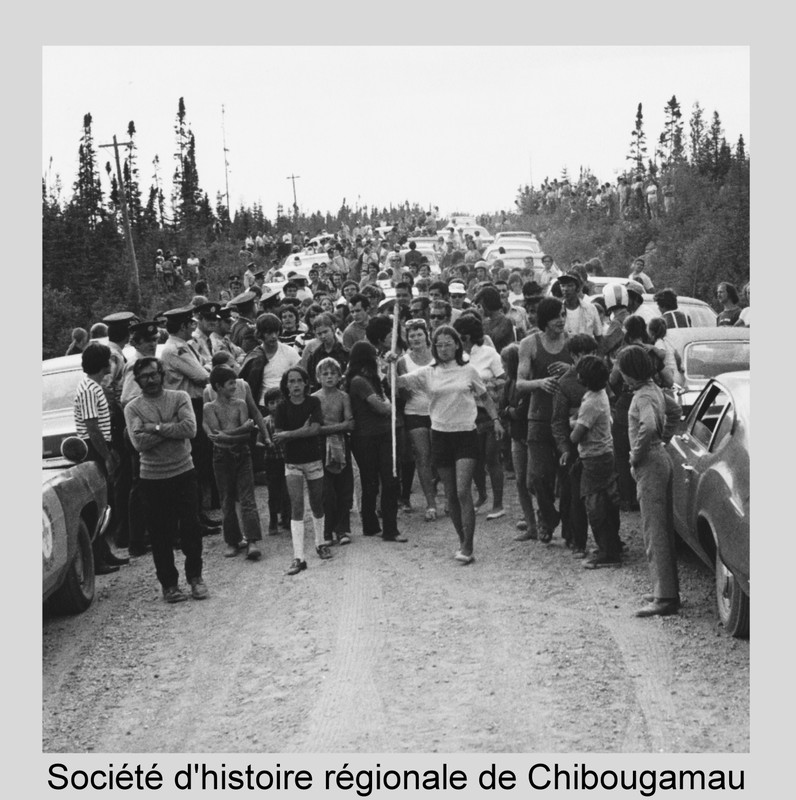 <p>On August 15, 1971, about 2000 people gathered in the R&eacute;serve Faunique Ashuapmushuan, known locally as the Chibougamau Park, to stage a blockade. Their efforts paid off: an agreement to completely upgrade the road was signed.<br /><br />1937: First winter road between Lac-Saint-Jean and Chibougamau<br />1945&ndash;1949: Construction of the first permanent road<br /><br />&ldquo;We drove through H&eacute;bertville, Roberval, Saint-F&eacute;licien and then into the Chibougamau Park ... We were driving along, and all of a sudden it was such a rough ride that I said to Cl&eacute;ment, &lsquo;Are you sure we&rsquo;re on the right road?` It was awful; when we rolled down our windows so we wouldn&rsquo;t be too hot and we met another car, we would have to hurry to roll up the windows. Then, when we arrived, our hair and faces were full of dirt.&rdquo;<br />&ndash; Monique Adams-Nadeau<br />De ressources et de vaillance, M&eacute;moire de la g&eacute;n&eacute;ration pionni&egrave;re du Nord-du-Qu&eacute;bec<br /><br />Full reference for the photo: Scene from the 1971 blockade. P33 Fonds Godefroy de Billy</p>