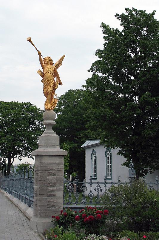 <p>L&rsquo;ange &agrave; la trompette annonce la R&eacute;surrection. L&rsquo;&oelig;uvre originale, maintenant conserv&eacute;e &agrave; l&rsquo;int&eacute;rieur de l&rsquo;&eacute;glise, a &eacute;t&eacute; sculpt&eacute;e par Henri Angers, en 1903. La sculpture ext&eacute;rieure actuelle, inspir&eacute;e de l&rsquo;originale, a &eacute;t&eacute; r&eacute;alis&eacute;e par Fabien Pag&eacute;, en 2009.<br /><br />Photo : &copy; Collection priv&eacute;e</p>