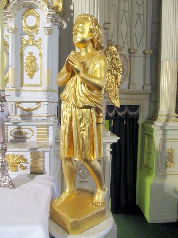 <p>De chaque c&ocirc;t&eacute; de l&rsquo;autel central, se tiennent deux anges adorateurs sculpt&eacute;s par Louis Jobin, en 1890, de m&ecirc;me qu&rsquo;un Christ en croix &eacute;galement attribu&eacute; &agrave; Jobin sur le mur gauche.<br /><br />Dans le fond du ch&oelig;ur, on peut voir deux m&eacute;daillons ex&eacute;cut&eacute;s en 1841, repr&eacute;sentant saint Pierre, &agrave; gauche, et saint Paul, &agrave; droite.<br /><br />Photo : &copy; SHSAD</p>