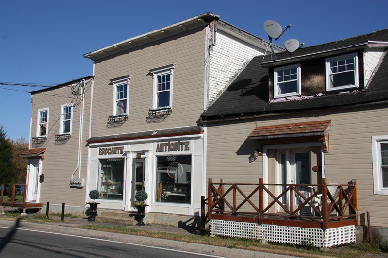 <p>This flat-roofed building dates from the early 20th century and formerly housed a general store on Route 323. The first shopkeeper was named John C. McLaughlin. Today, this heritage building houses an antique store full of old wares (source: Bergeron-Gagnon Inc., heritage inventory of the Laurentides RMC, 2013).</p>