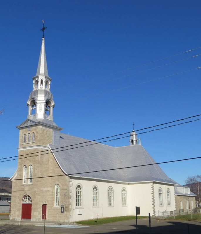 <p>The first church in Saint-Joachim, located near the large farm of Cap Tourmente, was burned down by the troops of James Wolfe during the British conquest of 1759. The pastor and seven parishioners lost their lives in the tragedy.<br /><br />A new church was built between 1771 and 1779 at the heart of the village, on the road connecting the key sites of the mill and the creamery. Today, this church has been classified as a historic monument. It owes its exceptional interior decoration to sculptor Fran&ccedil;ois Baillairg&eacute; and his son Thomas.<br /><br />Photo: Current church of Saint-Joachim (Bergeron Gagnon inc, 2015. Inventaire du patrimoine b&acirc;ti de la MRC de La C&ocirc;te-de-Beaupr&eacute;)</p>