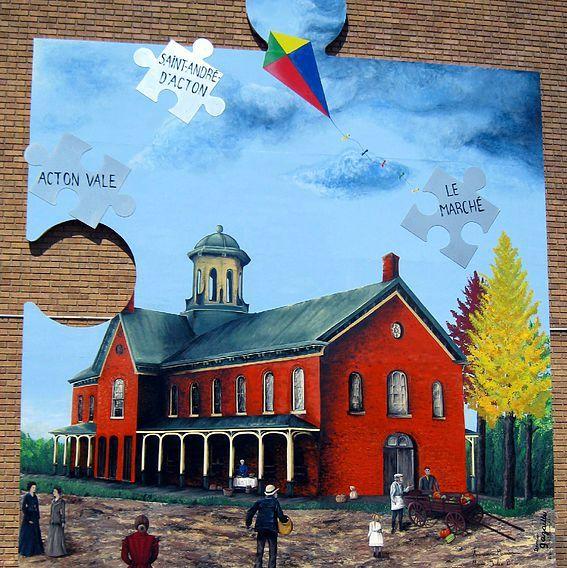 <p>Pour la cr&eacute;ation de la murale d&rsquo;Acton Vale, le conseil de ville a choisi Denise Gazaille, une artiste peintre professionnelle d&rsquo;Acton Vale qui, depuis plus de trente ans, expose partout au Qu&eacute;bec et qui a re&ccedil;u de nombreux prix de ses pairs pour ses &oelig;uvres.<br /><br />Elle a assur&eacute; la composition de cette murale en se basant sur les th&egrave;mes historiques d&eacute;termin&eacute;s par la municipalit&eacute; et l&rsquo;a r&eacute;alis&eacute;e en compagnie de deux stagiaires, Marie-Julie Blouin et Andr&eacute;anne Meunier, artistes peintres de la rel&egrave;ve.<br /><br />Gazaille est connue pour l&rsquo;int&eacute;gration de formes g&eacute;om&eacute;triques qu&rsquo;elle a ici repr&eacute;sent&eacute;es par des pi&egrave;ces de casse-t&ecirc;te symbolisant des morceaux d&rsquo;histoire de la municipalit&eacute;.<br />&nbsp;</p>