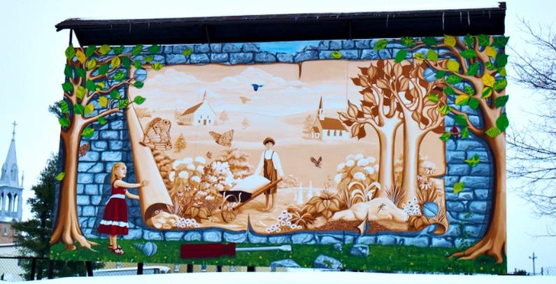 <p>Pour la cr&eacute;ation de la murale de Sainte-Christine, le conseil municipal a choisi Ryth&Acirc; Kesselring, une artiste peintre professionnelle native de Zezikon en Suisse, qui a re&ccedil;u plusieurs prix pour ses &oelig;uvres originales et audacieuses et qui diffuse son art au Qu&eacute;bec et en Suisse.<br /><br />Cette derni&egrave;re a assur&eacute; la composition de cette murale en se basant sur les th&egrave;mes historiques d&eacute;termin&eacute;s par la municipalit&eacute; et l&rsquo;a r&eacute;alis&eacute;e en compagnie de deux stagiaires, Genevi&egrave;ve Sabourin et Consuelo De La Bastida, artistes peintres de la rel&egrave;ve.<br /><br />Dans le cadre de la r&eacute;alisation de cette murale, Ryth&Acirc; Kesselring a int&eacute;gr&eacute; des arbres dont les feuilles ont &eacute;t&eacute; peintes par les enfants du village. Cet aspect participatif apporte un sentiment d&rsquo;appartenance aux villageois tout en repr&eacute;sentant l&rsquo;avenir de la municipalit&eacute;.</p>