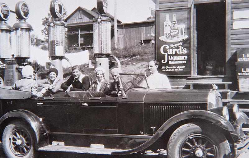 <p>Cette luxueuse automobile, stationn&eacute;e devant les pompes &agrave; essence de l&rsquo;&eacute;picerie de J. R. Lavigne, au lac Mercier, n&rsquo;a pas d&ucirc; passer inaper&ccedil;ue sur les chemins de la r&eacute;gion, au tournant des ann&eacute;es 1920. En 1929, &agrave; partir de Piedmont, seule une courte section de la route no 11 (l&rsquo;actuelle route 117) &agrave; Sainte-Agathe-des-Monts est rev&ecirc;tue de b&eacute;ton bitumineux; le reste est en gravier ou en terre. L&rsquo;automobile est alors un bien de luxe plut&ocirc;t fragile que seuls les plus riches peuvent s&rsquo;offrir. Plus on s&rsquo;&eacute;loigne des grandes villes, plus les m&eacute;caniciens et les stations d&rsquo;essence sont rares. Il faudra attendre la fin de la Deuxi&egrave;me Guerre mondiale pour que le nombre d&rsquo;automobiles enregistr&eacute;es au Qu&eacute;bec grimpe en fl&egrave;che et que le tourisme itin&eacute;rant s&rsquo;implante dans la fa&ccedil;on de vivre.<br /><br />&copy;&nbsp;Photo : Carte postale de la collection Marcelle Labelle, photographe inconnu.</p>