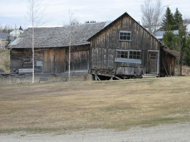 <p>On aper&ccedil;oit ici, une partie du b&acirc;timent ayant servi au moulin &agrave; scie dans les ann&eacute;es 1940. Le chemin de fer passant &agrave; proximit&eacute; effectuait un arr&ecirc;t pour laisser descendre des passagers ou pour le transport de billots de bois.<br /><br />Source : MRC Robert-Cliche</p>
