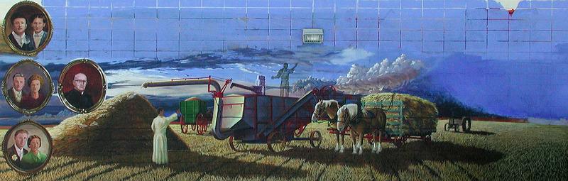 <p>Murale par Jacques Martel<br /><br />La murale repr&eacute;sente la famille de Joseph et Marie-Anne de Champlain pendant le temps des r&eacute;coltes annuelles &agrave; l&rsquo;heure du souper. C&rsquo;&eacute;tait une tradition d&rsquo;arr&ecirc;ter le battage et de se r&eacute;unir avec toute la famille pour manger. La famille de Champlain maintient l&rsquo;amour de la terre qui leur a &eacute;t&eacute; transmis par leurs anc&ecirc;tres. En 2013, les descendants cultivaient pr&egrave;s de 11 000 &acirc;cres (approximativement 4 600 hectares) dans la r&eacute;gion de Legal.</p>
