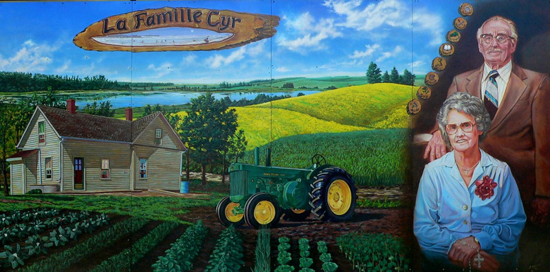Mural by Jacques Martel<br /><br />Roger and Maria Cyr were strong advocates of John Deer implements. Three of their sons followed their parents&rsquo; love of the land and became accomplished farmers.&nbsp; This mural also highlights the family&rsquo;s love of hockey in the top left corner, and their mom&rsquo;s strong spirituality is represented by Maria Cyr holding a rosary.&nbsp; Notice how the artist presented the trade mark of each child&rsquo;s interest in the wood carving.