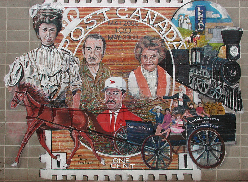 Mural by Dan Glen<br /><br />This mural celebrates 100 years of bilingual postal service in Legal. In 1900, M&eacute;n&eacute;sippe Massie was appointed the first postmaster. At first, mail was delivered once a week from Morinville via Pony Express. Later, the railway came which allowed the postal service to run three times a week. On the mural, we see the portraits of postmasters who have served for more than 25 years. They include Ben and Marie-Ange-St. Martin, Denis Limoges, and Rosaline Pelletier.&nbsp; We see Delphis Coulombe delivering the mail in his postal wagon. The children were added to depict the inclusion of youth in the project.