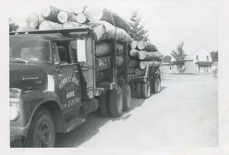 <p>Camion de bois stationn&eacute; dans la cour de &#39;Bois H.C. Leduc&#39; et en arri&egrave;re-plan, le magasin Pageau. (1954)</p>