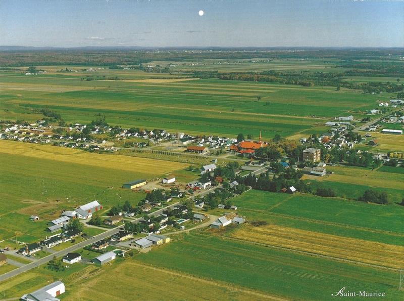 Une vue a&eacute;rienne du village de Saint-Maurice. Cette gravure &eacute;tait celle de juillet 2003 dans un calendrier promotionnel produit par Gazoduc TQM.<br />Il y a pr&egrave;s de 40 ans, une d&eacute;cision audacieuse des instances municipales et des membres de la fabrique allait changer le paysage visuel de notre village pour toujours. En installant une toiture orange aux trois &eacute;difices centraux du village, ceux-ci sont devenus, au fil des ann&eacute;es, un signe distinctif et reconnu de Saint-Maurice.