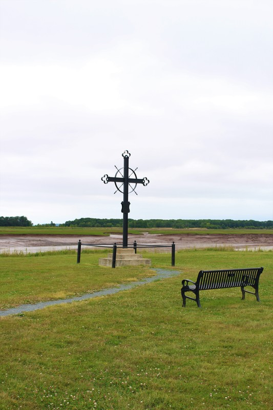 Located in Horton&#39;s Landing, this cross is a memorial site of the Deportation of the Acadians. &nbsp;From Hortonville, follow Wharf Road and&nbsp;the Cross will be located at the very end of the road, directly after a farm located on your right. Please Watch Out for farming equipment and children in the area!<br /><br />Forged from wrought iron in the Gothic style, the Cross bears the following inscription:<br />&quot;The dry bed of the creek which is in sight, a few paces in the marsh is the spot where the victims of the Expulsion of the Acadians of 1755 were embarked on the small boats to be rowed over to the transports lying at anchor in Minas Basin.&quot;<br /><br />A few meters away is a monument dedicated to the Planters who arrived in the region after 1755.<br /><br />Take the time to visit Mosquito Point. The working model dyke and modern aboiteau demonstrate Acadian techniques used to master tides and land in order to pursue their agriculture.<br /><br /><br />Photo: Pauline Naillon