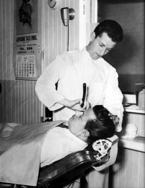 C&rsquo;&eacute;tait &agrave; l&rsquo;&eacute;poque o&ugrave; les barbiers faisaient r&eacute;guli&egrave;rement a barbe &agrave; leurs clients. Rares sont ceux qui offrent ce service de nos jours.&nbsp;<br /><br />Photo :&nbsp;Le barbier Roger Lupien et son client ,M. Gilles Ste-Marie, en&nbsp;juin 1955.