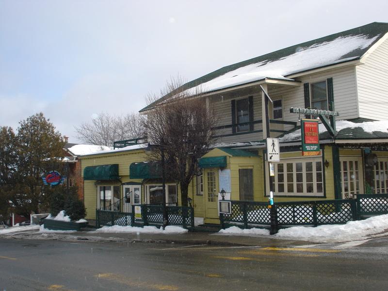 La maison du&nbsp;140, rue Morin.<br /><br />C&#39;est en 1900 qu&#39;un premier boucher, Wilfrid Marinier, s&#39;&eacute;tablit sur ce site. S&#39;y succ&egrave;dent tour &agrave; tour les Joseph Machab&eacute;e, Herv&eacute; Desjardins et Wilbrod Meilleur jusqu&#39;en 1923, date &agrave; laquelle s&#39;installe Auguste Ouimet (1894-1952). Ce dernier et, &agrave; sa suite, son fils Louis, y op&egrave;re la boucherie, puis une &eacute;picerie jusqu&#39;en 1976. Un restaurant occupe aujourd&#39;hui les lieux.<br /><br />Le commerce en d&eacute;clin de bois conserve beaucoup d&rsquo;&eacute;l&eacute;ments d&rsquo;origine, dont la magnifique galerie qui court sur deux fa&ccedil;ades. Le b&acirc;timent est recouvert d&rsquo;un toit &agrave; demi-croupe et d&rsquo;un avant-toit circulaire couvrant les deux galeries. On note &eacute;galement une abondante fenestration de bois et un oculus sur l&rsquo;une des fa&ccedil;ades.