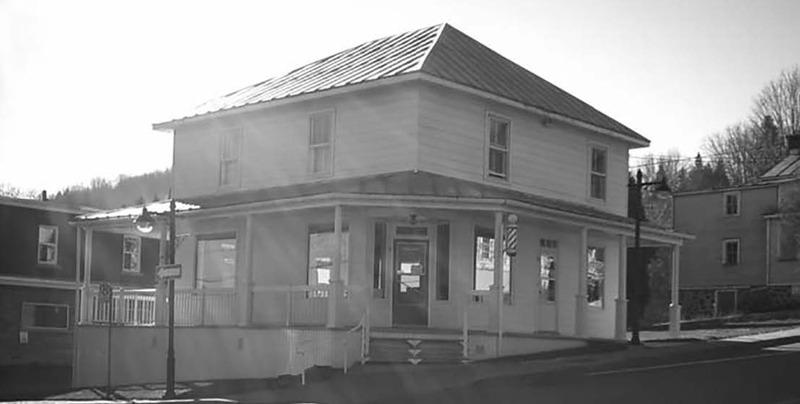 Maison du 50 et 52, rue Morin.<br /><br />Isra&euml;l Desjardins poss&egrave;de une terre qui couvre presque tout le bas du village. En 1884, elle est lotie et il en c&egrave;de un emplacement &agrave; Adolphe Lapointe qui y &eacute;rige une maison. Trois g&eacute;n&eacute;rations de Lessard vont tenir une boutique de barbiers dans sur ce site. Albert s&#39;est d&#39;abord install&eacute; en 1912 plus &agrave; l&#39;est, au coin de ce qui deviendra la route 11 (aujourd&#39;hui la 117). Son fils Guillaume (1903-1999) ouvre quant &agrave; lui une boutique peu apr&egrave;s avoir achet&eacute; l&#39;emplacement du coin de la rue Valiquette. Il y sera suivi par ses deux fils, Jacques et Guy, qui se d&eacute;partissent finalement de la boutique en 2004.<br /><br />Une maison qu&eacute;b&eacute;coise &agrave; toit &agrave; deux versants existait avant 1929, tel que le montrent les photographies anciennes. Un &eacute;tage et un toit en croupe s&rsquo;ajoutent &agrave; la maison depuis. On retrouve une imposte vitr&eacute;e au-dessus des portes principales.<br /><br />Source :&nbsp;Soci&eacute;t&eacute; d&rsquo;histoire et de g&eacute;n&eacute;alogie des Pays-d&rsquo;en-Haut