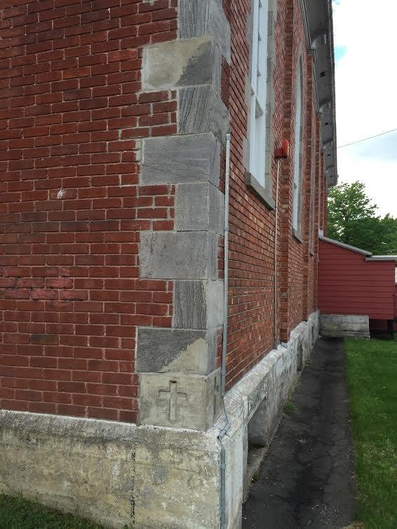 Des éléments de pierre grise structurent les différentes façades du bâtiment.