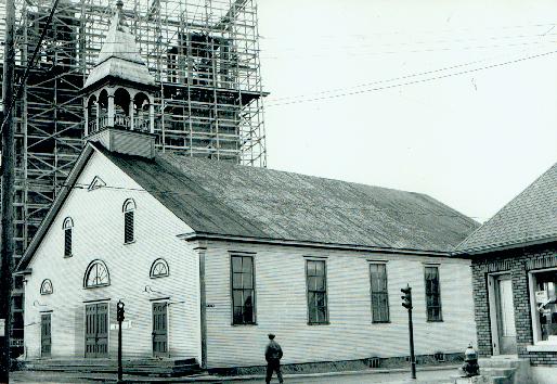 La nouvelle église en construction en arrière plan.