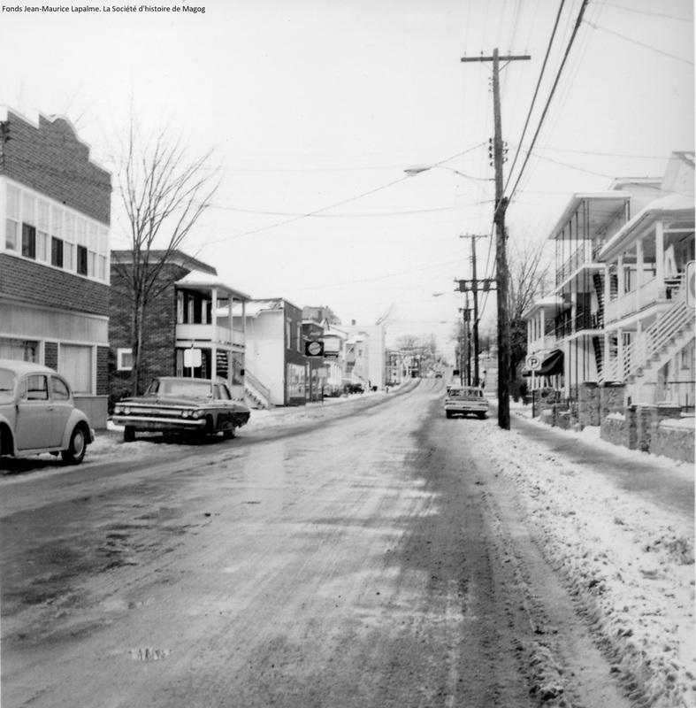 La rue Saint-Patrice&nbsp;porte deux autres noms&nbsp;avant d&rsquo;adopter officiellement cet odonyme du nom du patron de la paroisse. Sur le plan d&rsquo;arpentage de 1865, la rue prend son point de d&eacute;part au coin de la rue Sherbrooke. Elle est appel&eacute;e rue Goff, du nom d&rsquo;un propri&eacute;taire de terrains en bordure de la rue Sherbrooke.<br /><br />Quatre ans plus tard, Alvin Head Moore est engag&eacute; par la municipalit&eacute; de canton avec le mandat de tracer le prolongement de la rue Goff jusqu&rsquo;au chemin de Montr&eacute;al, l&rsquo;actuelle rue Merry.<br /><br />Plus tard, le prolongement de la rue Goff se fait sur les terrains de Goff pour les besoins d&rsquo;une nouvelle route qui m&egrave;ne &agrave; Sainte-Catherine-de-Hatley.<br /><br />Au m&ecirc;me moment, le tron&ccedil;on de la rue situ&eacute; &agrave; l&rsquo;endroit o&ugrave; nous nous trouvons est &eacute;largi avec comme objectif d&rsquo;en faire un centre urbain et un site propice aux processions religieuses.<br /><br />Un autre plan cadastral, celui de 1894, retient l&rsquo;odonyme de Pearl. Et, comme vous le savez d&eacute;j&agrave;, c&rsquo;est le nom du patron de la nouvelle &eacute;glise qui vient tout juste d&rsquo;&ecirc;tre &eacute;rig&eacute;e qui donne son nom d&eacute;finitif &agrave; la rue en 1896.&nbsp;<br />&nbsp;