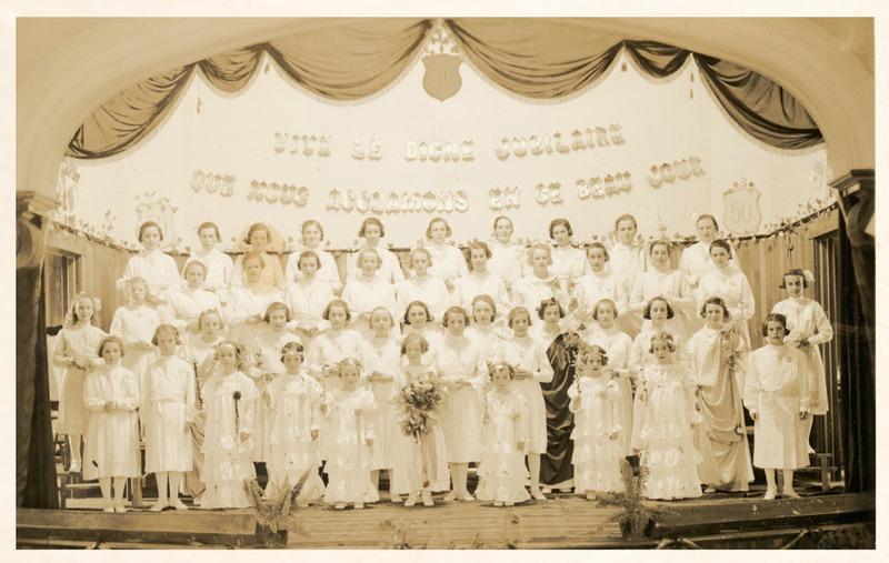 <p>Les pensionnaires et les externes du couvent de Cacouna chantaient et jouaient la com&eacute;die sur la sc&egrave;ne de ce th&eacute;&acirc;tre de la salle paroissiale. En 1938, quarante-cinq jeunes filles de la congr&eacute;gation des Enfants de Marie soulignaient le jubil&eacute; d&rsquo;or de Mgr Louis T. Landry.<br /><br />Source photo:<br />Photo document &laquo; Les repr&eacute;sentations th&eacute;&acirc;trales &raquo; p. 1<br />Photo: coll. Richard Michaud</p>