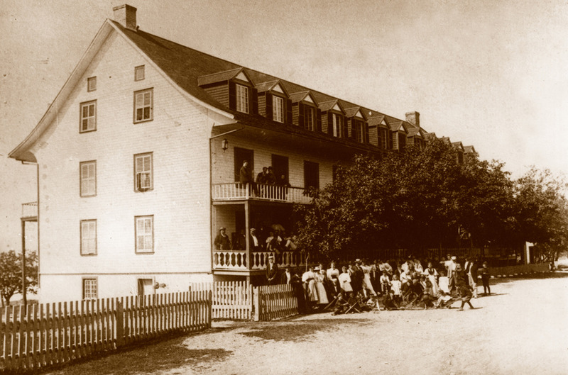 <p>H&ocirc;tel Mansion House, vers 1900.<br /><br />&Agrave; cette &eacute;poque, le Saint-Laurent ne permettait pas que le transport des marchandises.&nbsp; D&egrave;s 1851, le Rowland Hill, un bateau &agrave; vapeur qui avait son port d&rsquo;attache &agrave; Qu&eacute;bec, faisait escale &agrave; Cacouna pour d&eacute;barquer des passagers qui venaient s&rsquo;y refaire une sant&eacute; gr&acirc;ce aux bains de mer.&nbsp; Devant l&rsquo;afflux de touristes, M. Dionne d&eacute;cida, en 1852, de faire construire un grand &eacute;tablissement qu&rsquo;il loua, au fil des ans, &agrave; plusieurs h&ocirc;teliers.<br /><br />En 1911, Joseph B&eacute;langer, surnomm&eacute; &laquo; Monsieur Klondike &raquo; apr&egrave;s qu&rsquo;il se f&ucirc;t enrichi lors de la ru&eacute;e vers l&rsquo;or, acheta l&rsquo;h&ocirc;tel et la maison.&nbsp; Les deux b&acirc;timents &eacute;taient alors connus sous le nom de Mansion House.&nbsp; Ils demeur&egrave;rent la propri&eacute;t&eacute; de la famille B&eacute;langer pendant 53 ans.&nbsp; Malheureusement, l&rsquo;h&ocirc;tel fut compl&egrave;tement d&eacute;truit par un incendie en janvier 1966.<br /><br />Cet h&ocirc;tel, construit en 1852-1853,&nbsp; porta au cours des ann&eacute;es le nom de St.George&rsquo;s Hotel, Jean&rsquo;s Hotel, Kakouna Hotel et Mansion House (vers 1890).<br /><br />Source photo:<br />Mus&eacute;e du Bas-Saint-Laurent, Fonds Belle-Lavoie<br />&nbsp;</p>