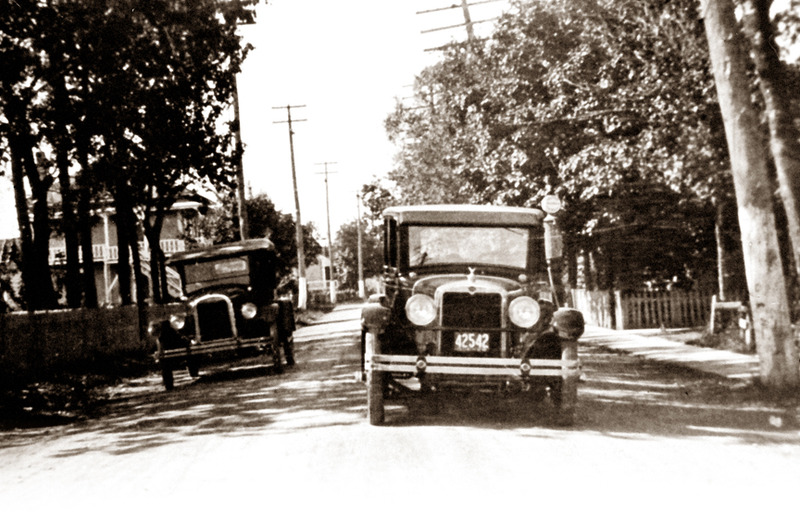 <p>Vers 1925, les automobilistes arr&ecirc;taient &agrave; la pompe &agrave; essence du magasin d&rsquo;Eus&egrave;be Rivard, &agrave; droite sur la photo.<br /><br />Dans la premi&egrave;re partie du 20e si&egrave;cle, quand l&rsquo;automobile fit son apparition sur les routes de campagne, monsieur Rivard accomoda les voyageurs, en particulier les touristes, en offrant de la gazoline.&nbsp; C&rsquo;&eacute;tait le plus jeune de la famille, Paul-&Eacute;mile, qui servait &agrave; la pompe jusque tard le soir. Au temps de la prohibition, dans les ann&eacute;es 1930, il arrivait parfois, dans la veill&eacute;e, que des contrebandiers en d&eacute;placement s&rsquo;y arr&ecirc;tent.&nbsp; Ne voulant pas participer &agrave; un trafic illicite et encourir des risques s&eacute;rieux, les Rivard abandonn&egrave;rent la distribution de la gazoline.<br /><br />Source photo:<br />Coll. Jacques Michaud, ptre</p>