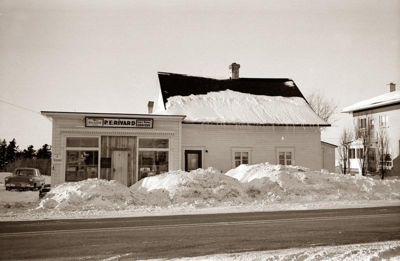 <p>Fa&ccedil;ade du magasin g&eacute;n&eacute;ral de Paul-&Eacute;mile Rivard, vers 1970.<br /><br />En 1925, Paul-&Eacute;mile acheta, d&rsquo;une dame Lavoie, la maison voisine de celle de son p&egrave;re.&nbsp; Il la fit agrandir en longueur pour annexer son magasin et avoir, en fa&ccedil;ade, deux vitrines. De 1925 &agrave; 1970, avec sa femme Marie-Blanche-Rose Castonguay, ils y accueillirent les acheteurs cherchant des produits de pharmacie et de quincaillerie.&nbsp; M&ecirc;me les plus jeunes s&rsquo;y arr&ecirc;taient pour s&rsquo;y procurer leurs friandises pr&eacute;f&eacute;r&eacute;es.<br /><br />Source photo:<br />Photo : Lynda Dionne</p>
