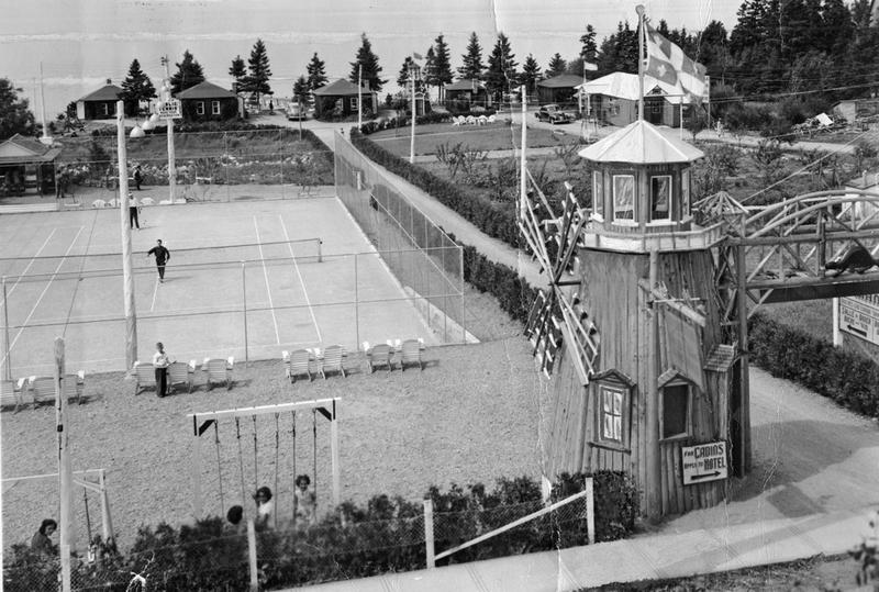 <p>Terrain de tennis du Manoir Cacouna avec sa cantine, vers 1947. En arri&egrave;re-plan, une vingtaine de cabines furent construites en bordure de la falaise.<br /><br />Le couple Dionne n&rsquo;avait pas oubli&eacute; les sportifs, puisqu&rsquo;en juillet 1947, ils inauguraient un terrain de tennis non loin du petit moulin-&agrave;-vent servant &agrave; l&rsquo;accueil des voyageurs. Un voisin, Louis-Philippe Perron, pendant une dizaine d&rsquo;ann&eacute;es, loua cette installation sportive de juin &agrave; septembre.&nbsp; Aid&eacute; par son fils a&icirc;n&eacute; Yvon, il entretenait et posait les lignes et le filet.&nbsp; &Agrave; la cantine, on accueillait les amateurs de sport et on louait, &agrave; l&rsquo;occasion, des raquettes et des balles.&nbsp; Apr&egrave;s avoir disput&eacute; une bonne partie, les sportifs ne manquaient pas d&rsquo;y commander une liqueur froide.<br /><br />Source photo:<br />Coll. Famille L&eacute;on Dionne</p>